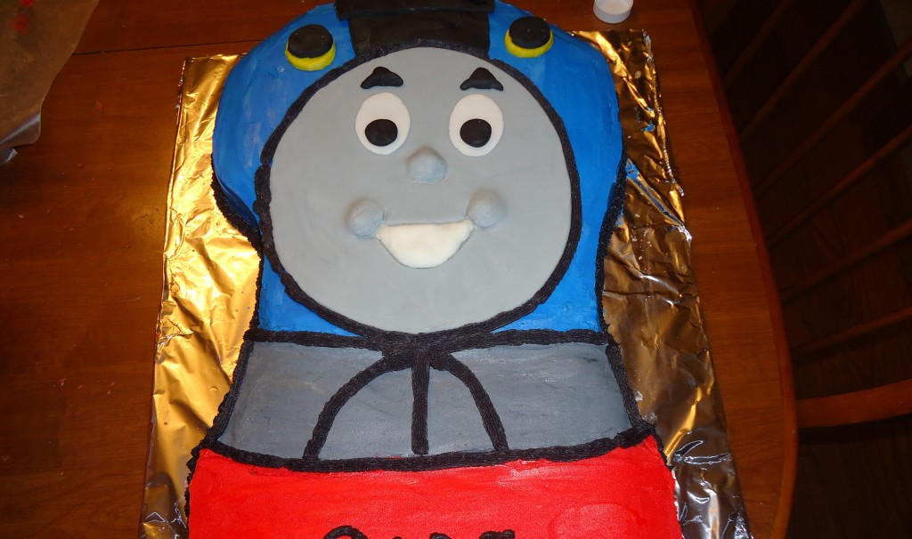 Thomas the Train birthday cake on a foil tray with smiling eyes and mouth