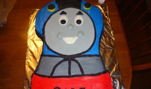 Thomas The Train Birthday Cake on a foil covered sheet with smiling eyes and mouth