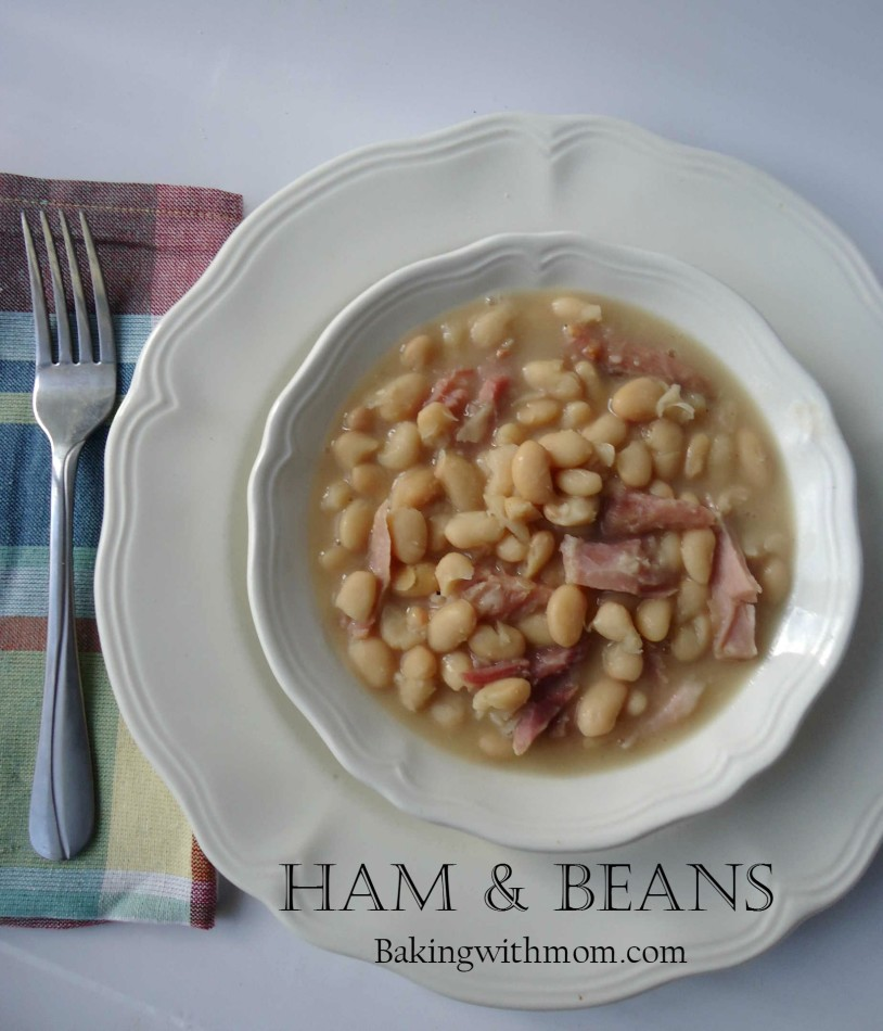 ham and beans in a white bowl with a fork and napkin off to the side