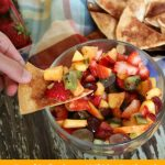 Fruit salsa with strawberries, kiwi and a variety of fruit in a clear bowl