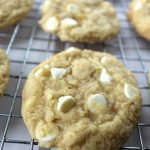 Soft and Chewy White Chocolate Chip Cookies on a cooling rack on a white board