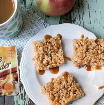 Crispy apple cider treats with a caramel drizzle on a white plate. Apple cider in a white mug