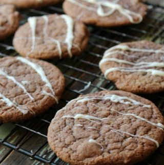 Hot Chocolate Cookies with almond bark drizzle on a cooling rack