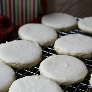 White Velvet Cookies with cream cheese and creamy white frosting on top of a baking sheet
