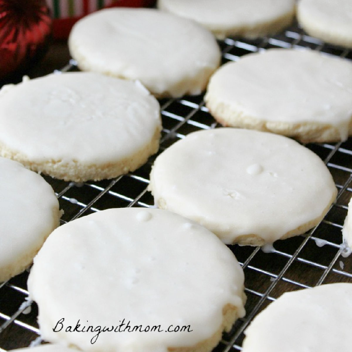 white frosting covered cookies sitting on a cooling rack