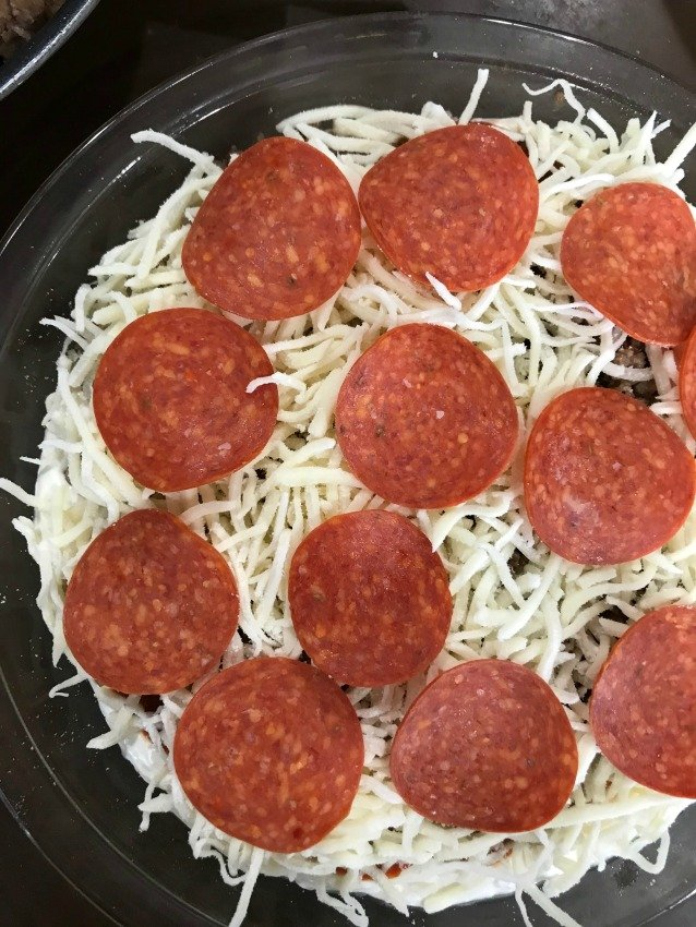 Pepperoni and cheese on top of a clear pie plate for hot pizza dip