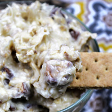Cookie dough dip in a clear bowl with a graham cracker