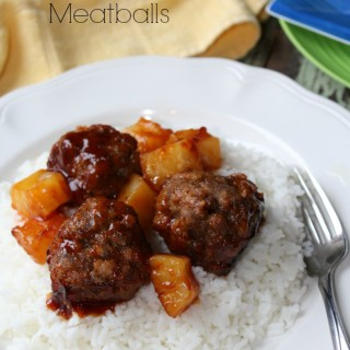 meatballs and pineapple on a bed of rice on a white plate
