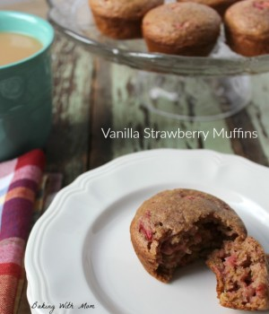 strawberry muffin on a white plate with a cup of coffee