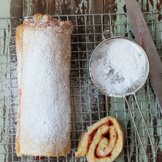 jelly roll with powdered sugar on a baking rack