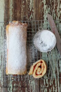 strawberry jelly roll with powdered sugar and strawberry swirl