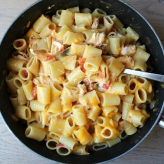 Pasta noodles in a frying pan with chicken and tomatoes