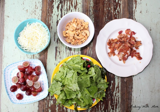 Lettuce on a plate with bacon, cashews, cheese and grapes