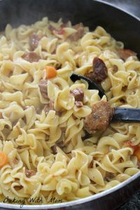meat and noodles and carrots in a frying pan