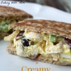 chicken salad sandwich on a white plate with grapes and celery