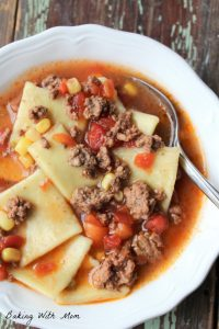 Zesty Hamburger Dumpling Soup in a white bowl with tomatoes and hamburger