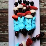 Easter kabobs with grapes, strawberries, berries on a white plate
