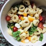 Italian Tortellini Salad in a bowl with spinach, cheese, tomatoes