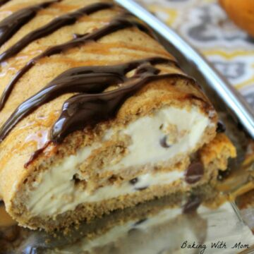 Pumpkin ice cream roll on a silver platter with chocolate drizzled on top