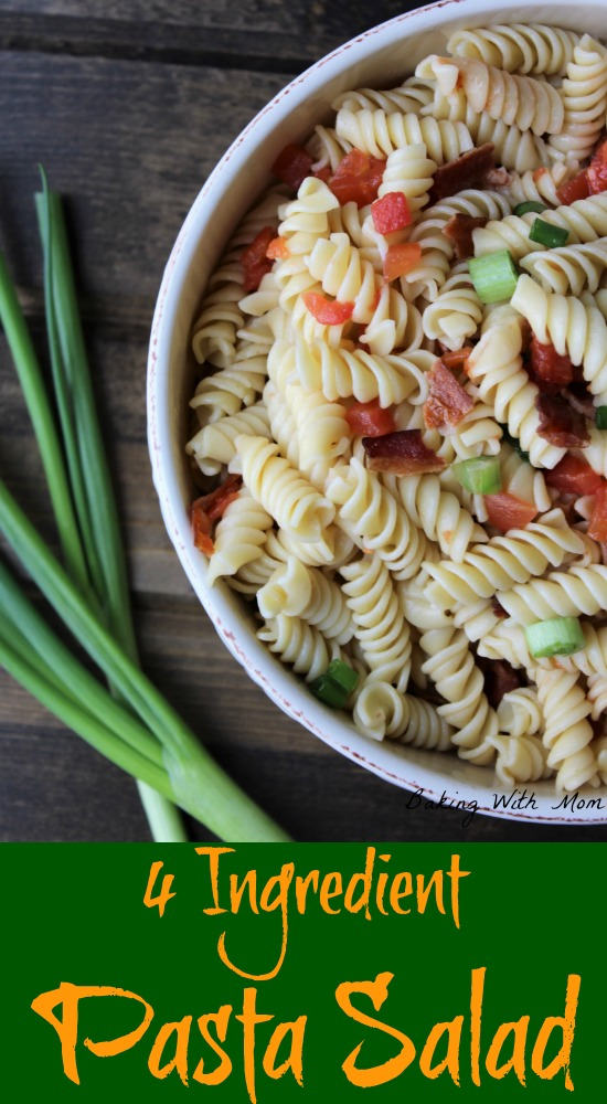 pasta, green onions, tomatoes, bacon in a cream colored bowl on a brown backdrop