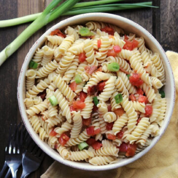 pasta salad in a cream bowl with green onions