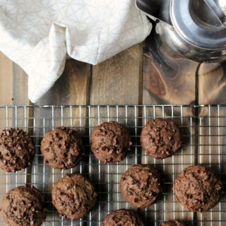 chocolate muffins on a cooling rack and a silver pitcher