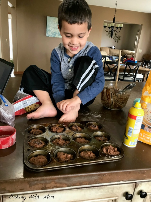 Child with muffins on the counter