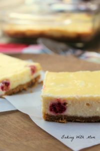 cheesecake squares slices with raspberries on waxed paper