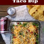 Easy Layered Taco Dip with hamburger, chips and cheese in a serving dish