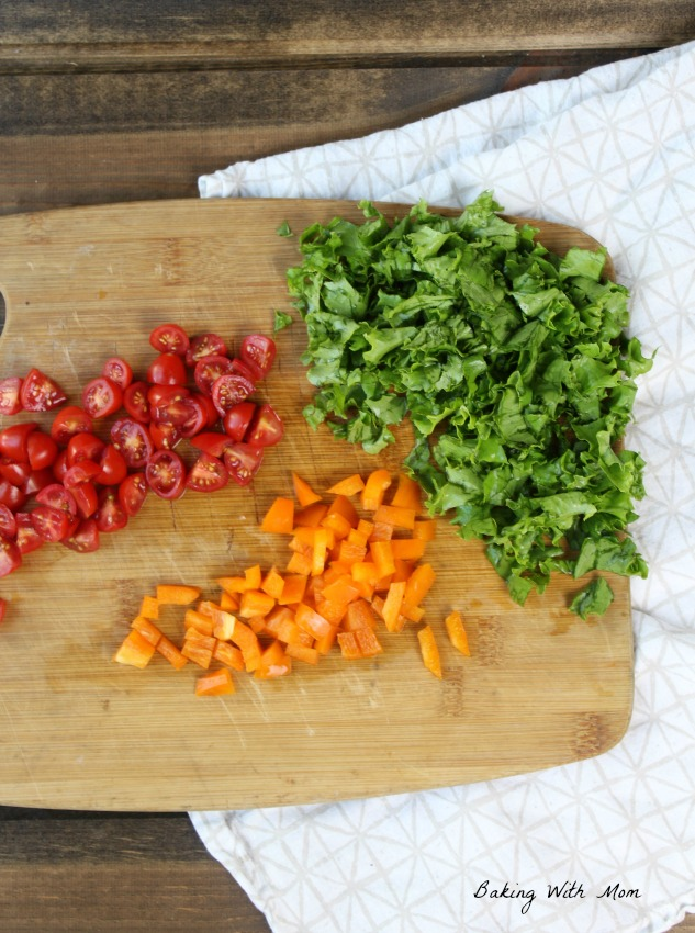 Orange peppers and tomatoes and lettuce on cutting board