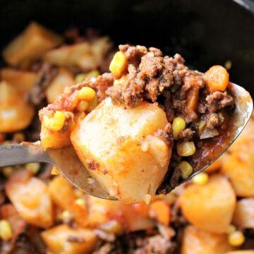 hamburger, potatoes, corn and carrots on a serving spoon
