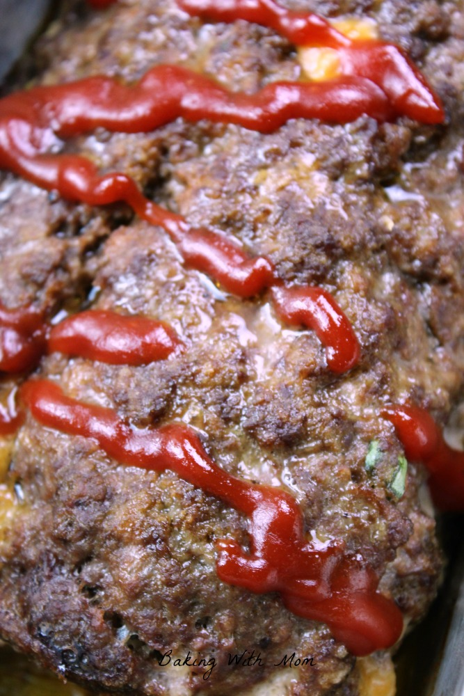 Stuffed Cheesy Meatloaf with cheddar cheese and green onions in a loaf pan