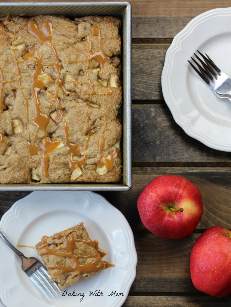 Apple cake in a 9x13 pan next to two apples