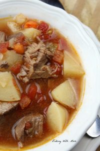 Crock Pot Vegetable Beef Soup in a white bowl with tomatoes, beef and potatoes