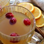 Spiced Apple Cider in clear cups with oranges in background