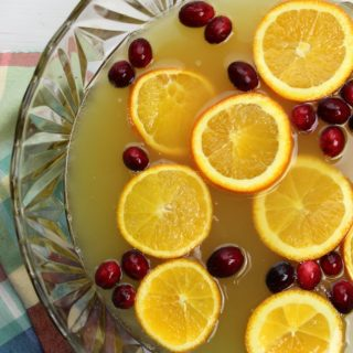 Holiday Orange Juice Punch with orange slices and cranberries in a punch bowl
