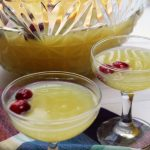 Holiday Orange Juice Punch in clear glasses with cranberries