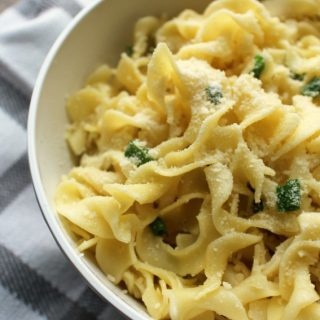 Cheesy Buttered Noodles with chopped green onions in a white bowl