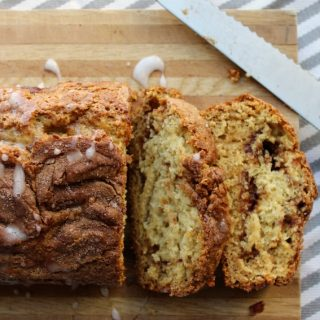 Quick Cinnamon Swirl Bread on cutting board with frosting drizzled on top