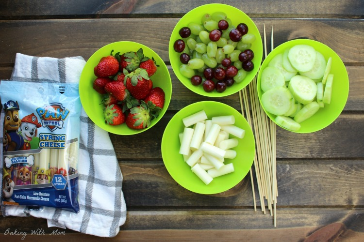 Strawberries, grapes, cucumbers and string cheese in green bowls