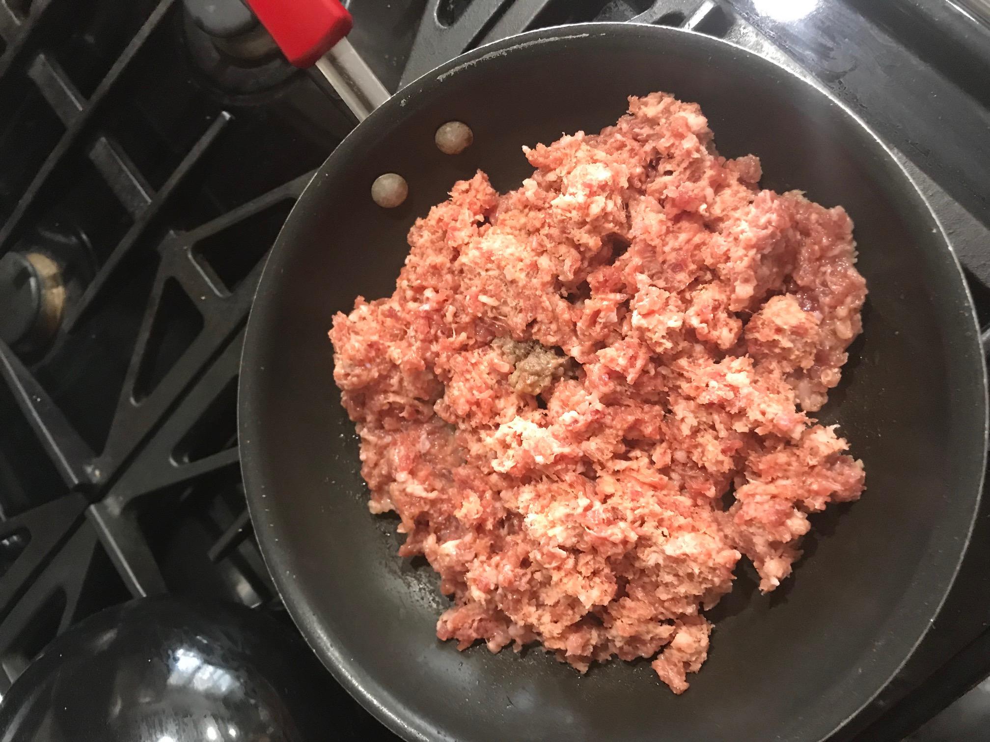 Sausage frying in a frying pan