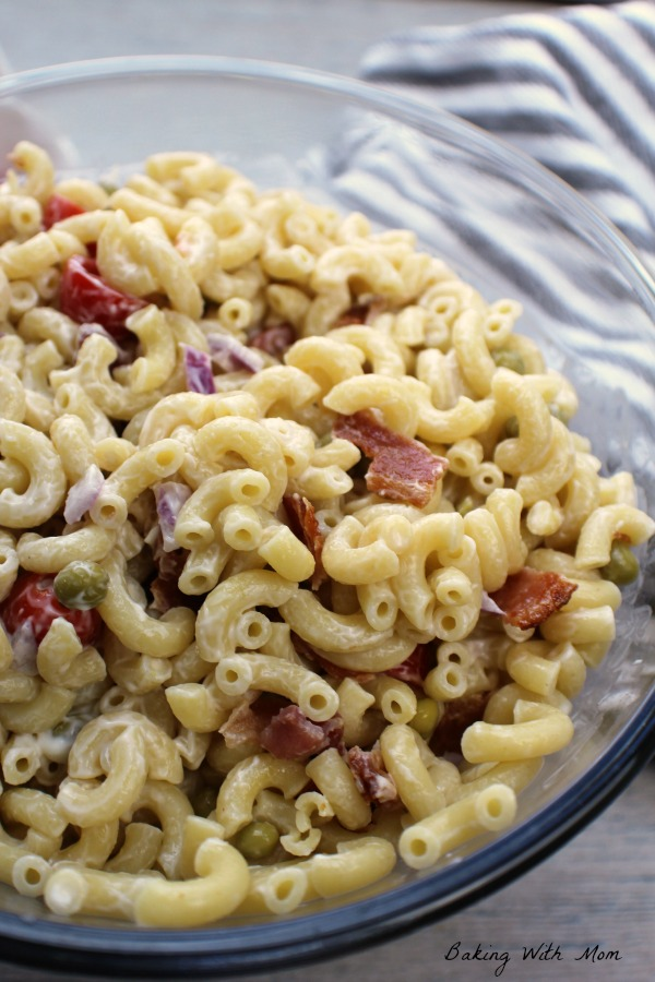 Macaroni salad in a clear bowl with bacon and tomatoes