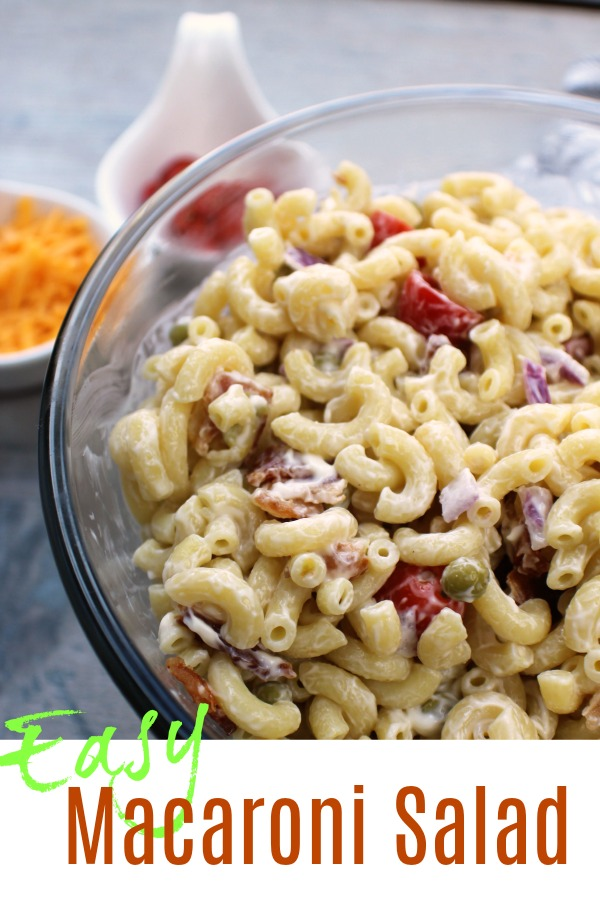Easy Macaroni Salad in a clear bowl with tomatoes and cheese on the side