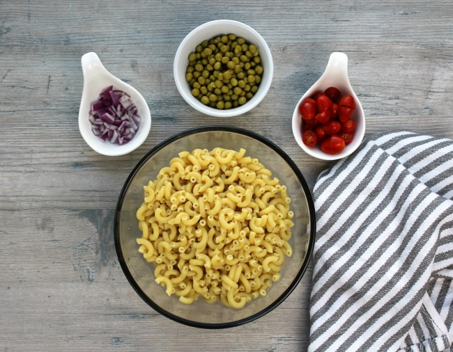 A bowl of macaroni noodles, peas, tomatoes and onions