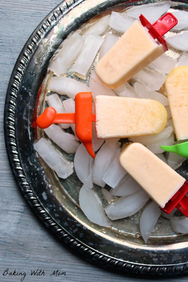 Homemade Orange Creamsicle Popsicles on a tray with ice cubes