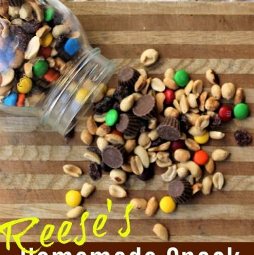 Snack mix with peanuts, m&m's, reese's peanut butter cups on a cutting board