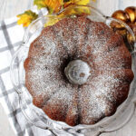 pumpkin cake on a cake platter with fall leaves besides