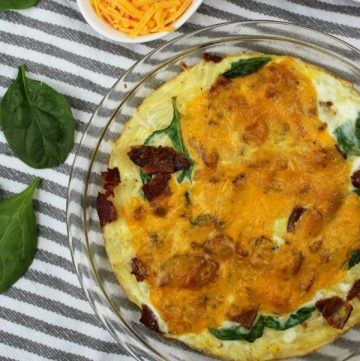 Bacon Spinach Quiche in a clear pie pan with cheese and spinach leaves on the side