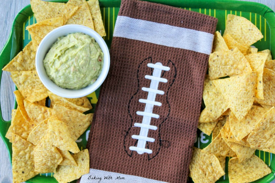 Football towel and easy homemade guacamole dip with chips on a tray
