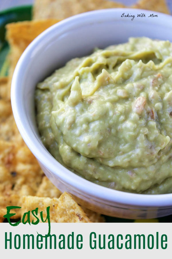 Homemade guacamole in a white bowl with tortilla chips on the side